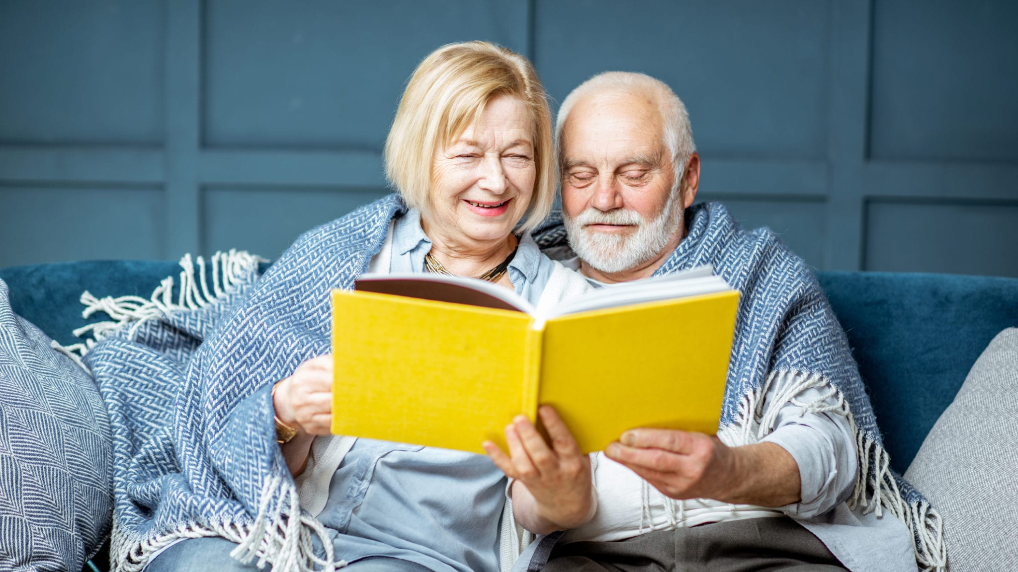 Senior Couple Reading Book On The Couch At Home